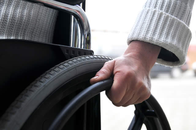 close up of a person's hand on a wheelchair wheel